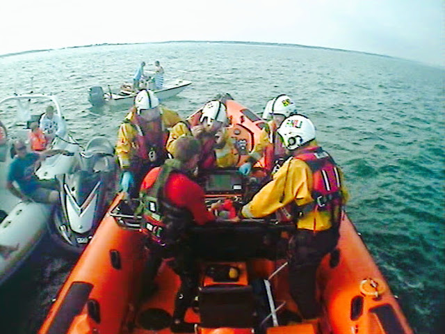 An injured jetskier being transferred to the ILB on the helicopter scoop stretcher. 17 May 2014 Photo: RNLI/Poole ILB