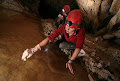 Katie Dent water sampling in 1954 passage, Whiterock Cave | photo © Robbie Shone