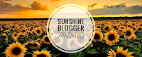 Inumerous sunflowers in a field at sunset which is the image used to indicate the Sunshine Blogger Award