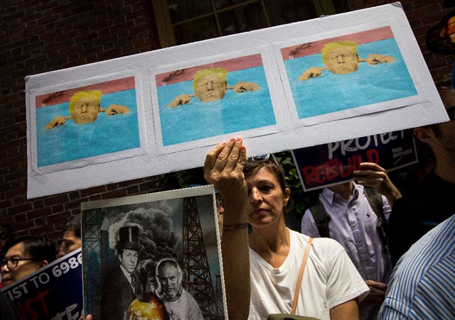 A protester holds a graphic showing Trump as the 'three wise monkeys' who 'see no evil, hear no evil, speak no evil', as he is inundated by flood waters. Photo: AFP