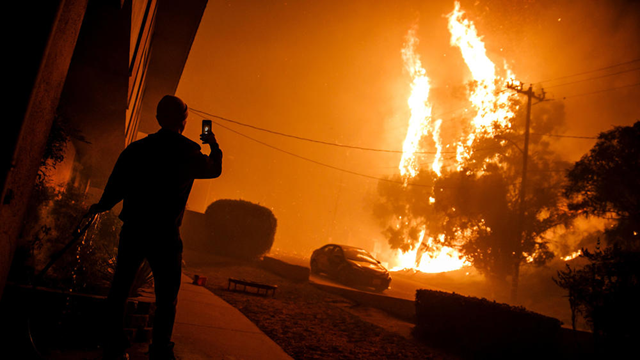 A man waters the front of a building and takes a picture of flames approaching homes in Ventura, 4 December 2017. Photo: Marcus Yam / Los Angeles Times