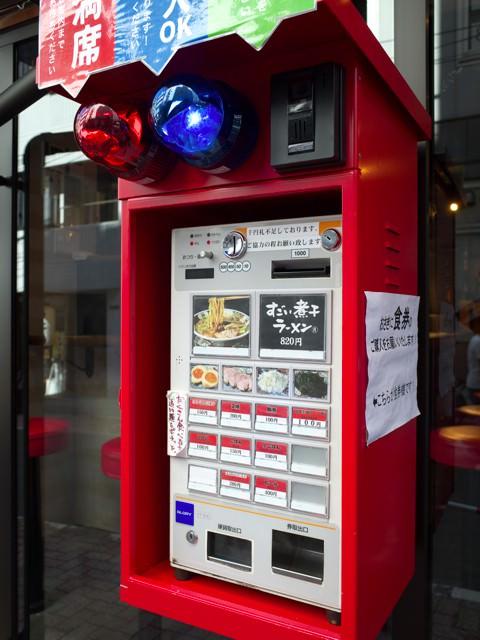 店頭にある券売機。上には赤と青のパトライトがついてて満席状態がわかるようになってる。