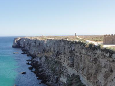 Utsikt utover en odde med bratte kanter ned mot havet. Et fyrtårn på tuppen av odden.