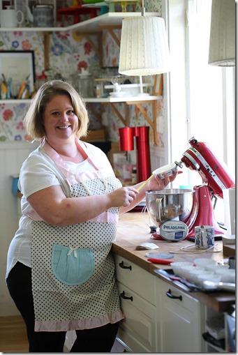 Jag står redo att baka i ett prickigt förkläde vid min röda Kitchen Aid