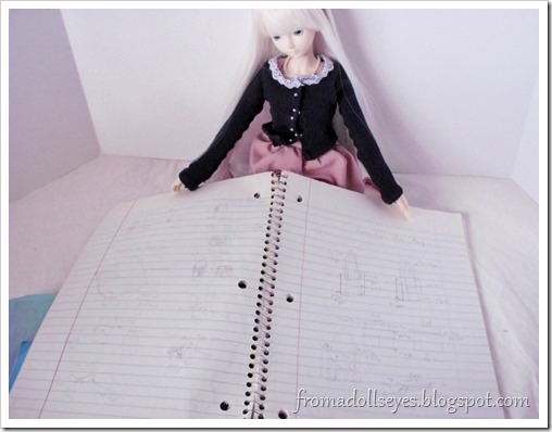 A ball jointed doll looking at craft ideas in a notebook.
