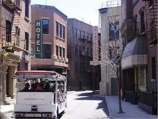 En buss som kjører gjennom en gate «gamle» murbygninger.