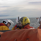 9 October 2011. Poole lifeboat Crew Members Dave Leabourne and Dave Armstrong receive a briefing from Deputy Second Coxswain Glen Mallen and the winchman from helicopter 106 prior to winching. Photo: Poole RNLI/Ade