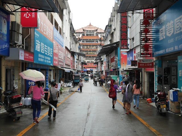 people walking down a narrow street in Changde