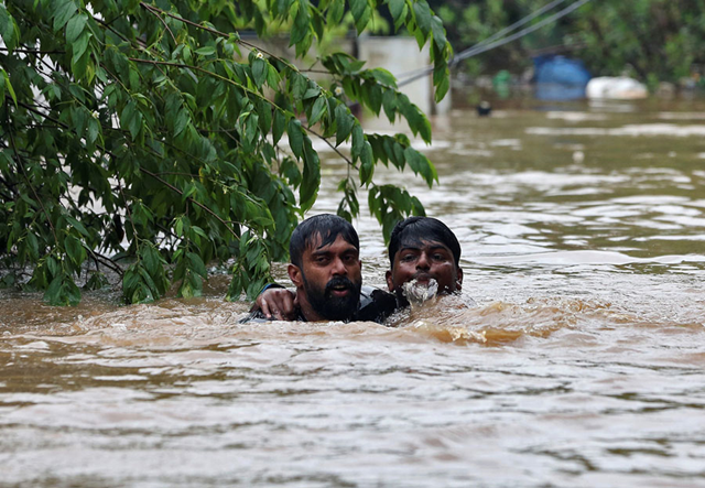 A man rescues a drowning man from a flooded area on the outskirts of Kochi, India, on 16 August 2018. Photo: Sivaram V. / Reuters