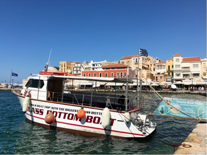 En liten passasjerbåt med sitteplasser på akterdekket fortøyd i havnen.