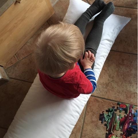 Kind sitzt auf dem Seitenschläferkissen