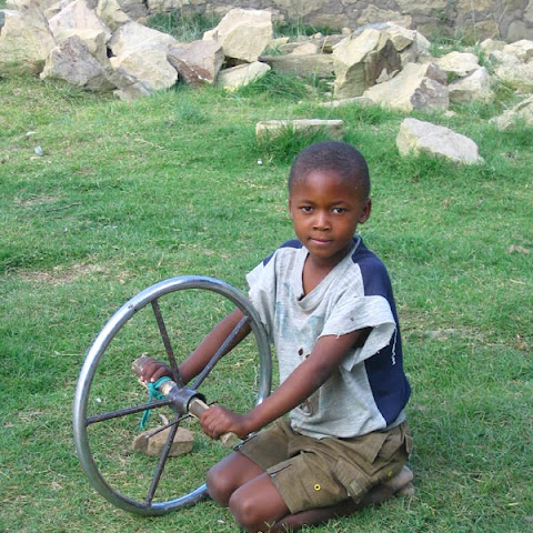 A boy in Lesotho plays with an old steering wheel