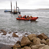 An RNLI crew member looks on as the submerged vehicle is investigated - 27 October 2014.  Photo credit: Sally Adams/Bournemouth Echo