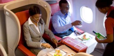 A man and a woman been served a meal on a First Class flight