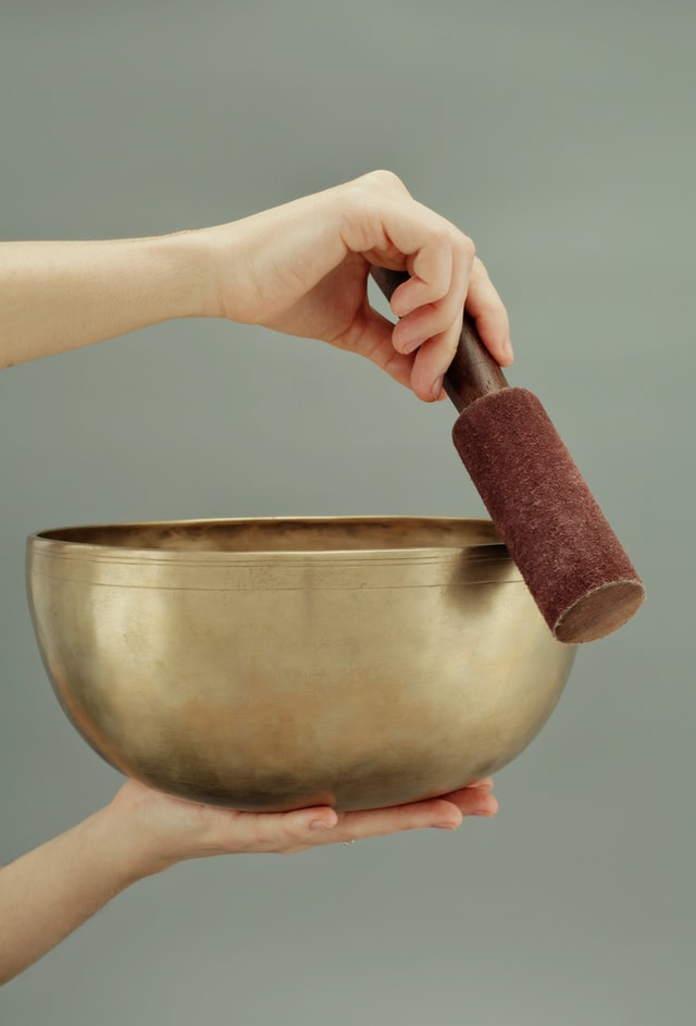 Therapist holding a Tibetan Singing Bowls during a healing session.