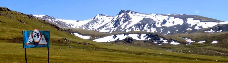 Verkehrsschilder vor Schneebergen auf dem Kalmak-Ashu-Pass (3445 m), Kirgistan
