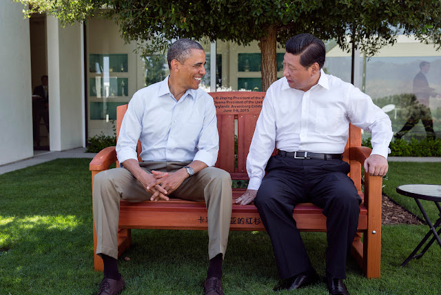 Barack Obama and Xi Jinping sit on a bench