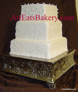 Four tier square white fondant unique wedding cake with sugar pearls and royal icing scroll piping