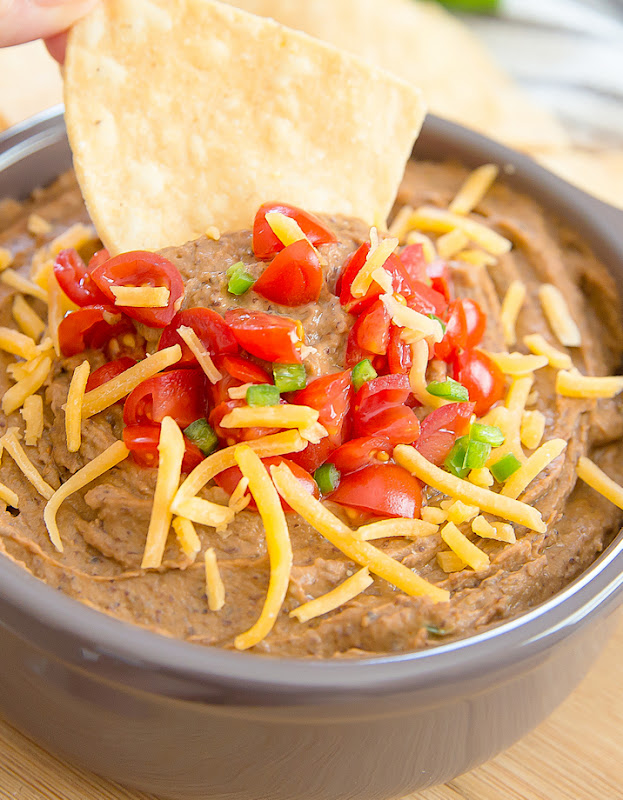 close-up photo of a tortilla chip being dipped into a bowl of Southwest Black Bean Hummus Dip