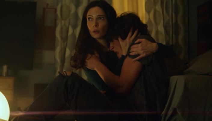 Lois Lane sentada no chão do quarto abraçando Jordan, que está tendo uma crise de ansiedade e chora.