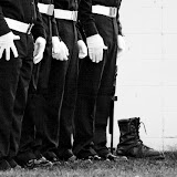 Jon Lomb, Jeremiah Arvish, Brendan Underwood, and Jonathan Kotka stand at attention beside a pair of empty boots in rememberance of fallen soldiers during the Frenchtown Veterans' Day celebration on November 11, 2011. Photo by Bekhi Spika.