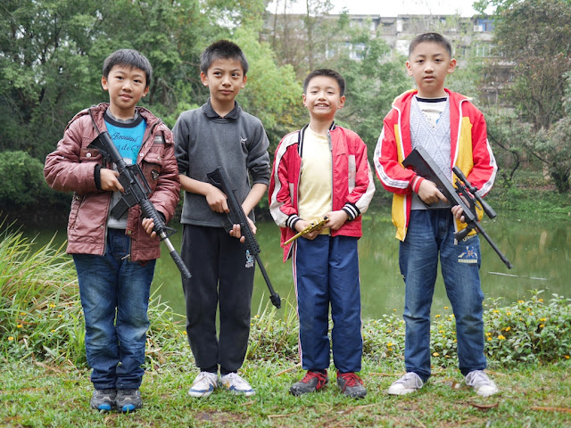 four Chinese boys holding toy guns