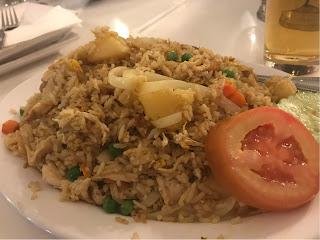En haug med en blanding av ris, kylling og ananasbiter.