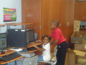 Photo: Jihad showing Kaleya the computer in his classroom