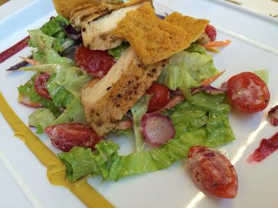 Tykke skiver med kylling over salat- og tomatbiter.
