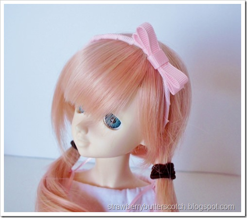 Pink ribbon headband for a doll.