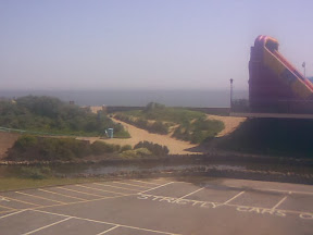 car park with beach & sea vista behind & giant bouncy slide amusement