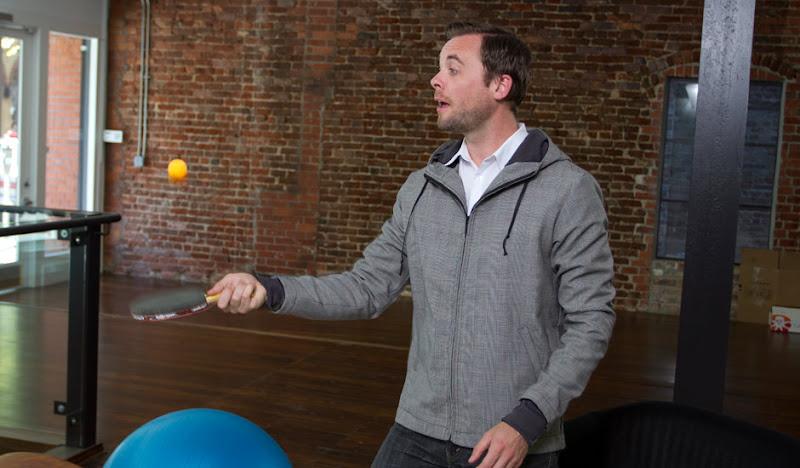 Gray Executive Hoodie Playing Ping Pong
