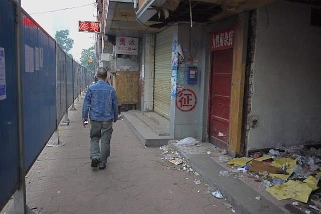 man walking next to a building marked for demolition at Beizheng Street in Changsha, China