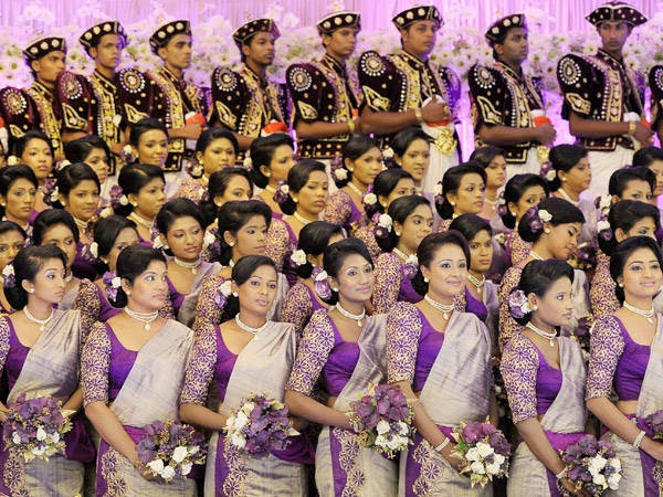 Sri Lankan bridesmaids and best men pose for photographers during the Guinness World Record-breaking wedding of unseen couple Nisansala and Nalin in Negombo, some 30kms north of Colombo, on November 8, 2013.