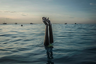 Woman in water with arms raised snapping fingers
