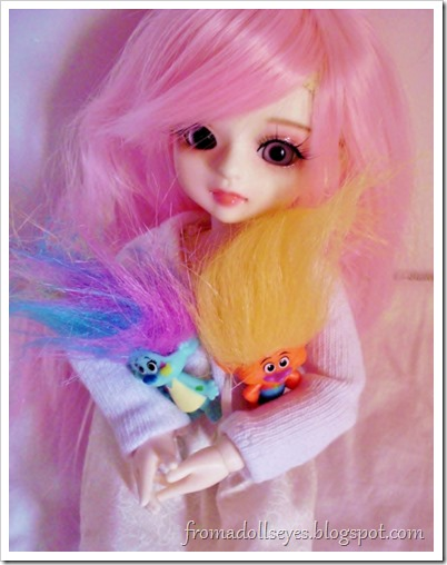 A ball jointed doll holding her troll dolls