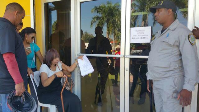 Mujer se encadena en puerta del Banco Agrícola de Dajabón alegando estafa