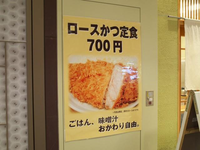 店頭に貼られた「ロースかつ700円、ごはん味噌汁お代わり自由」と書かれたポスター