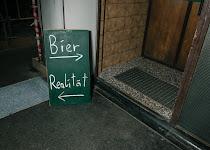 bord tussen 2 deuren met opschrift: bier rechts, realität links