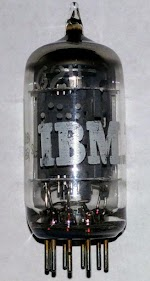 IBM 6211 vacuum tube: a dual triode. The pins plug into a socket on the top of the tube module. The plates are visible inside the tube. The number 6211 is faintly visible near the top of the tube.