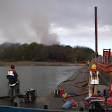 20 April 2012 - Firefighters lay out hoses and pumps to pump seawater to the site of a devastating fire on Green Island. Photo: RNLI/Poole Lifeboat Station Anne Millman