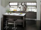 cucina modello TIME di Snaidero in legno rovere dark con isola snack e pensili con vetri scorrevoli. I pensili possono anche essere in legno con ante battenti. Le ante hanno dei filetti  in alluminio che la rendono leggera.