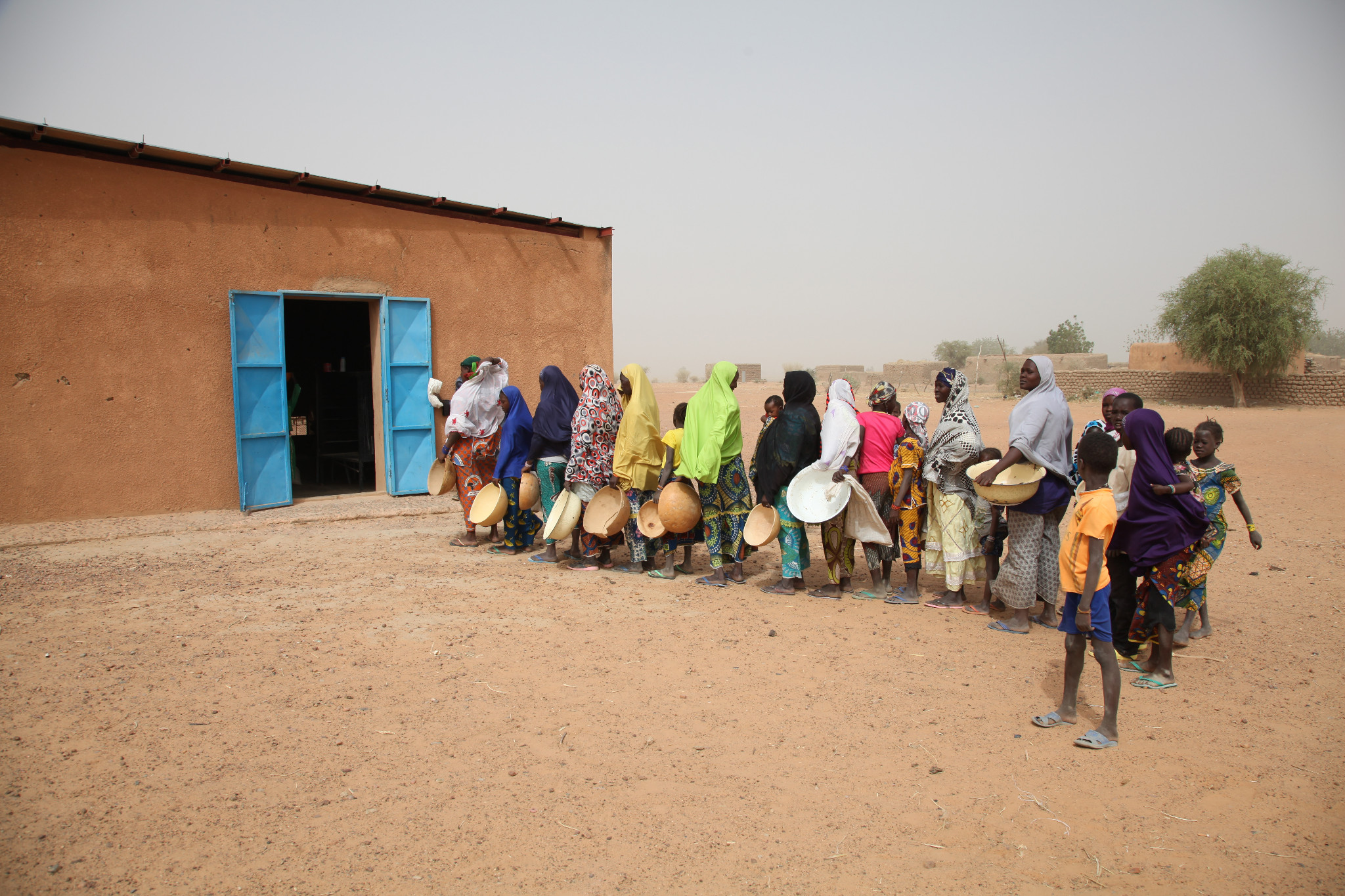 "Photo: Nigerien villagers line up to collect food from a Plan-funded cereal bank in Tillaberi District. ""Now we all depend on the cereal bank,"" says the village chief. ""The families here go and make money and then buy millet from the cereal bank. Normally we do not open it until June when the lean period starts. But this time round we have opened it because we cannot leave it closed while the villagers are suffering due to food shortage."""