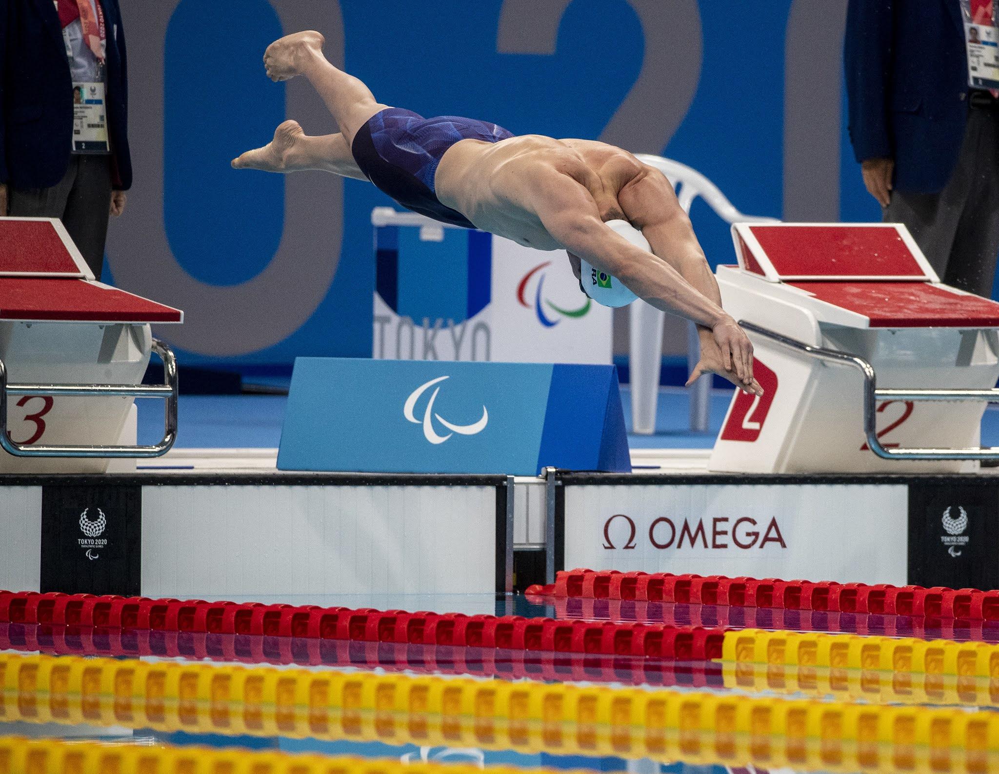 Phelipe Rodrigues salta na piscina usando bermuda azul e touca branca