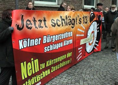 Demonstranten mit großem Transparent: »Jetzt schlägt's 13! Kölner Bürger schlagen Alarm…«.