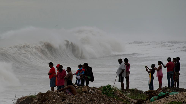 People stand on the coast watching the surf produced by Hurricane Matthew, on the outskirts of Kingston, Jamaica, 3 October 2016. A hurricane warning is in effect for Jamaica, Haiti, and the Cuban provinces of Guantanamo, Santiago de Cuba, Holguin, Granma, and Las Tunas - as well as the southeastern Bahamas. Photo: Eduardo Verdugo / AP Photo