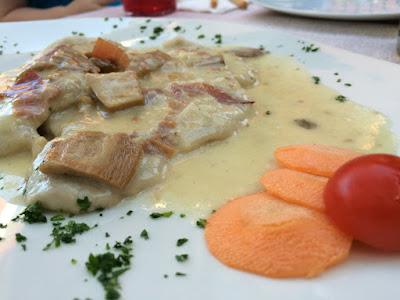 Et tynt stykke med lyst kjøtt, dekket med en hvis saus med sopp- og skinkebiter.