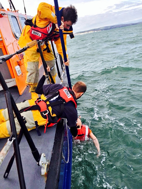 Volunteer crew members Dave Bursey (prone) and Chris Speers (stood up) retrieve the dummy casualty from the water - 26 October 2014.  Photo credit: RNLI/Oli Mallinson