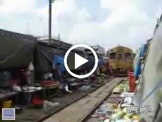 train_runs_through_bangkok_market_1.wmv