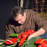 Una cistella clàssica amb espuma molla fou el suport per a contruir un centre allargat amb roses vermelles, anthuriums i unes llargues strelitzies.